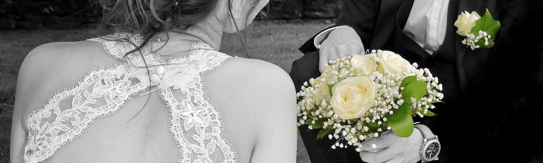 Photo de jeunes maries originale en noir et blanc avec le bouquet de la mariee en couleur