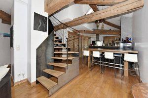 loft vue escalier et espace cuisine avec poutres apparentes