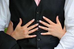 mains mariee sur gilet du marie